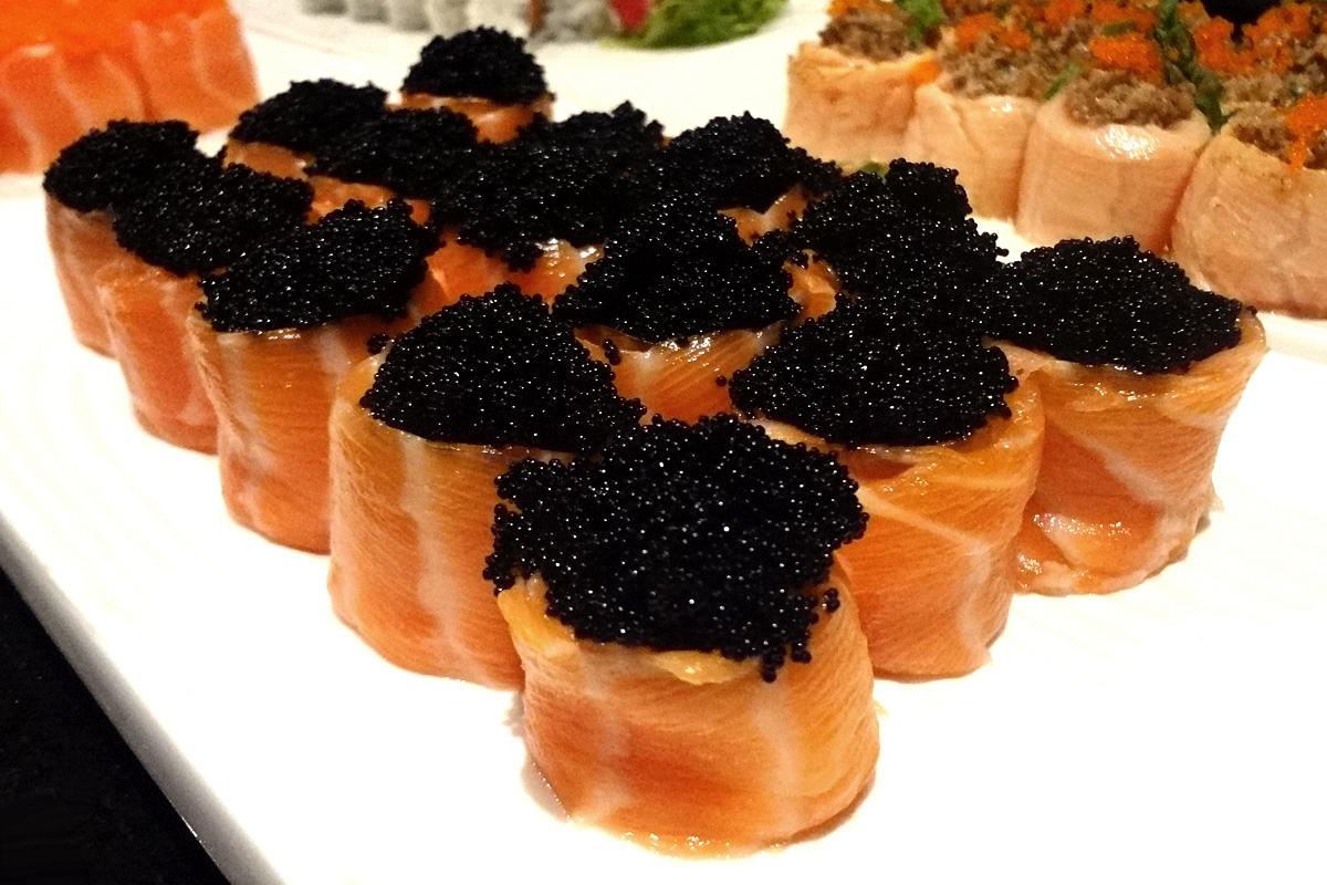 #pracegover: Foto com vários jyos enrolados com salmão e ovas pretas sobre eles em prato de porcelana branca.
